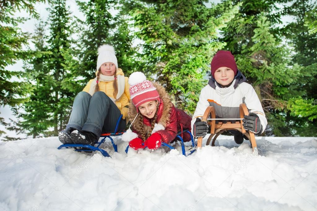 Boy and girls sitting on their sledge