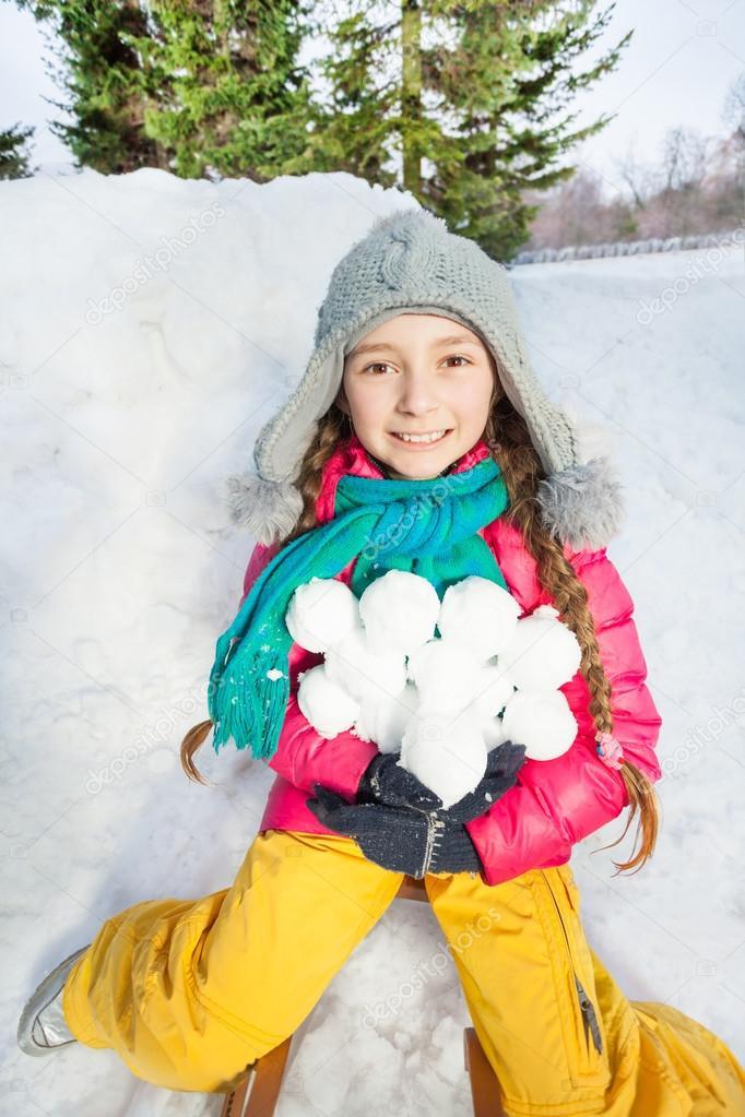smiling girl holding snowballs