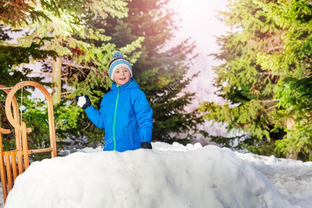 Happy boy stands hiding in snow