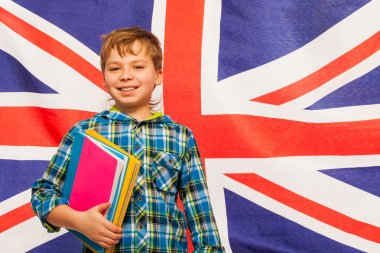 Schoolboy with textbooks against English flag