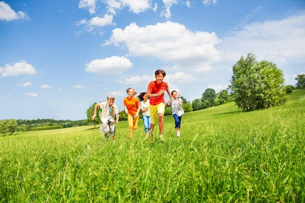 Funny children running together in field
