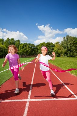 Girls run and reach ribbon