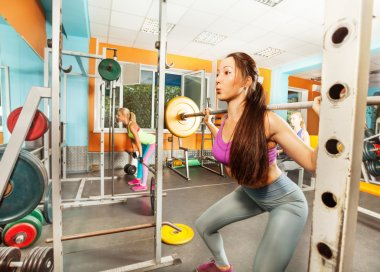 Asian woman showing barbell Squat