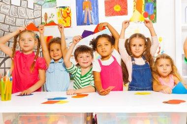 Kids showing cardboard shapes