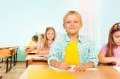 Usměvavý chlapec sedí ve třídě