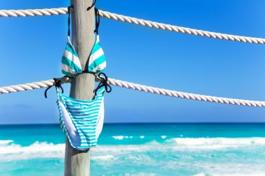 Stripped bikini hanging on ropes of pier