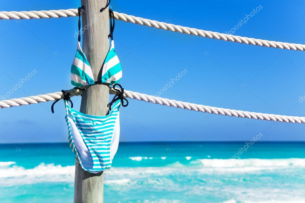 Stripped bikini hanging on ropes of pier