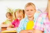 Fotografie Junge im Klassenzimmer mit anderen Schülern