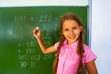 Girl writing mathematics equation