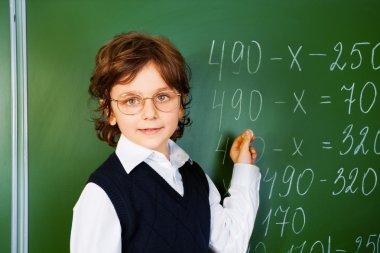 Boy with glasses near blackboard