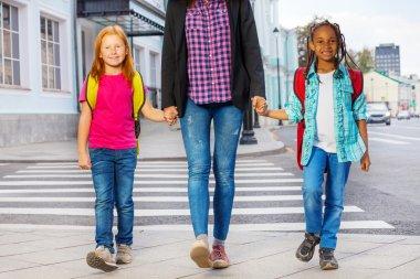 Kids with woman walking on street