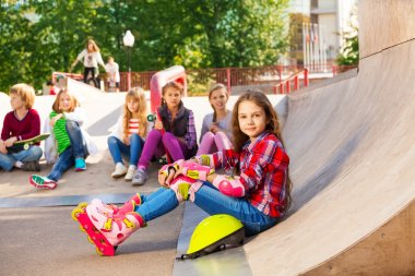 Girl with helmet wearing in-line skates sitting