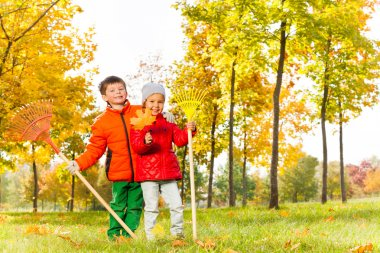 Boy and girl with rakes in park
