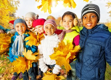 Happy children with beautiful leaves bunches
