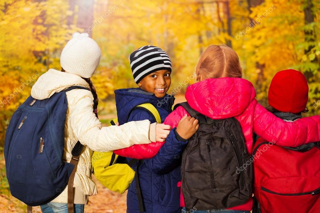 Kids standing close with rucksacks