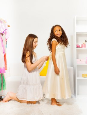 Girl helps to fit dress