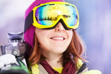 Woman in mask holding ski