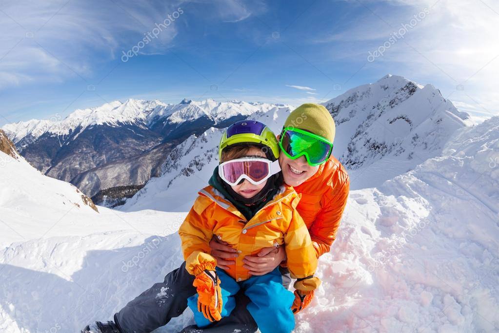 Little skier and father sit on mountain