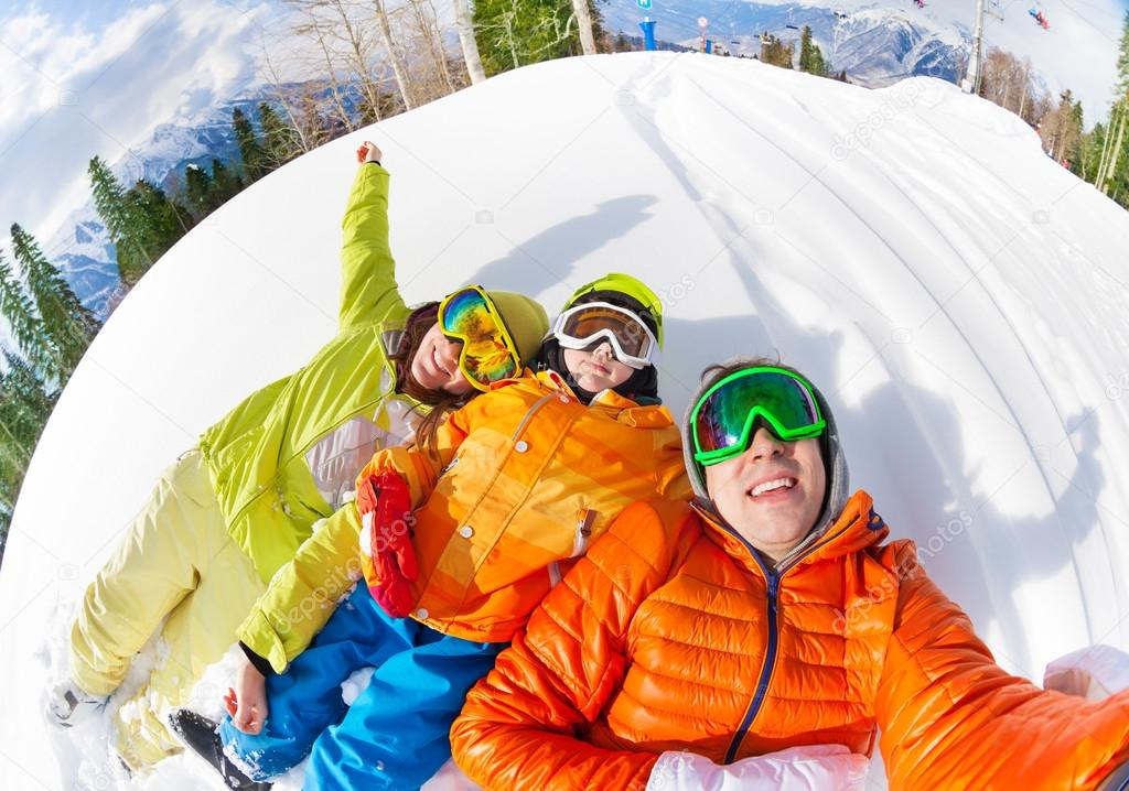 Happy family laying in snow