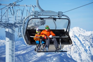 Father and boy sit in ski lift
