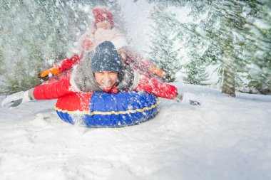 Friends on snow tube in winter