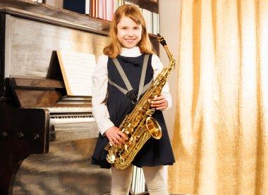Happy girl holds alto saxophone