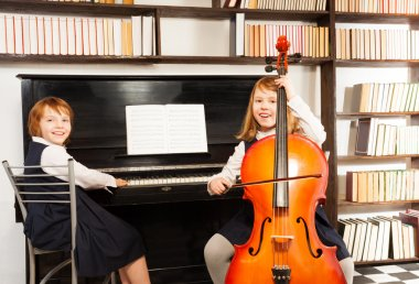 Girls in dresses playing cello and piano