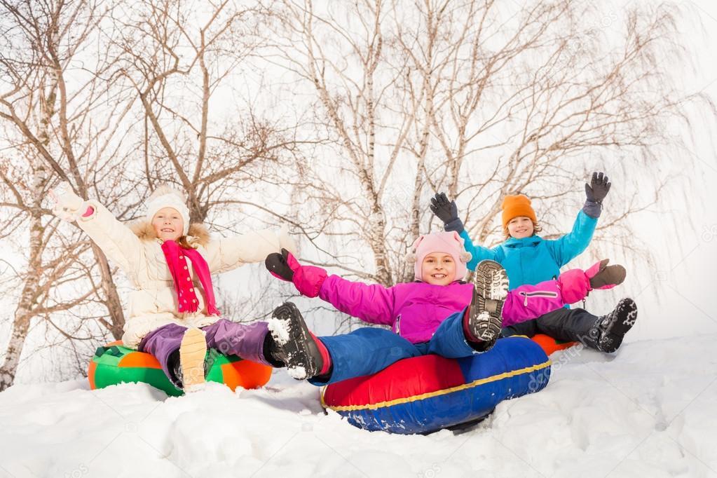 Excited children sliding down on tubes