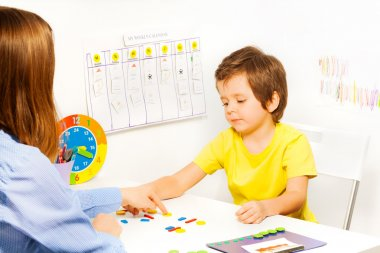 Boy putting colorful shaped coins