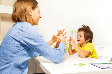 Boy exercises putting fingers with therapist