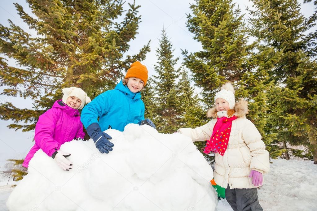 happy kids build snow wall