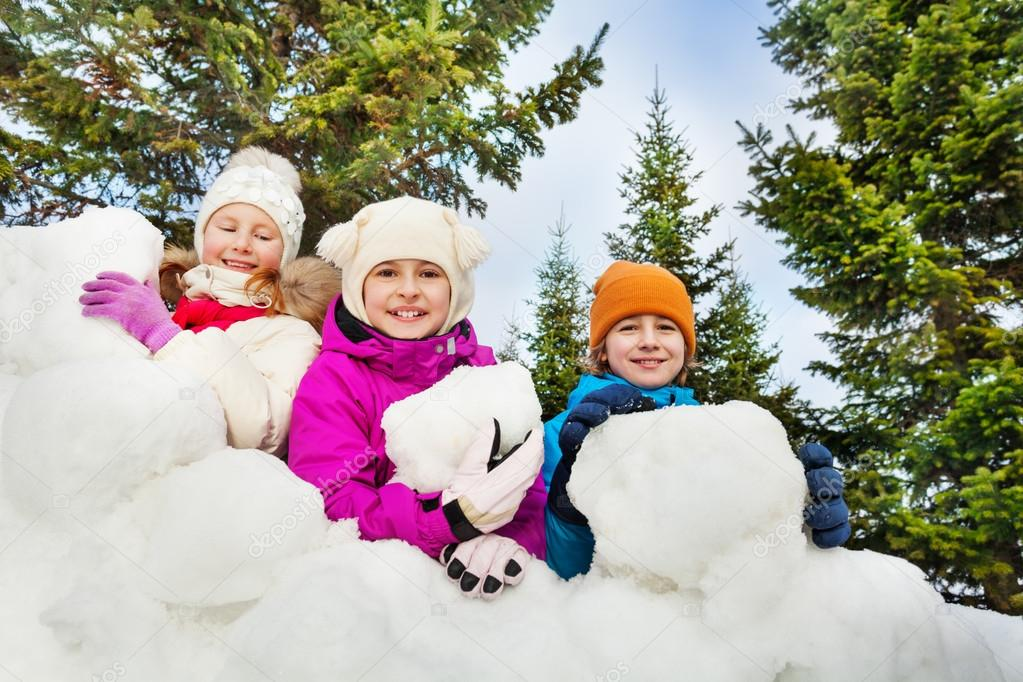 happy kids behind snow fort
