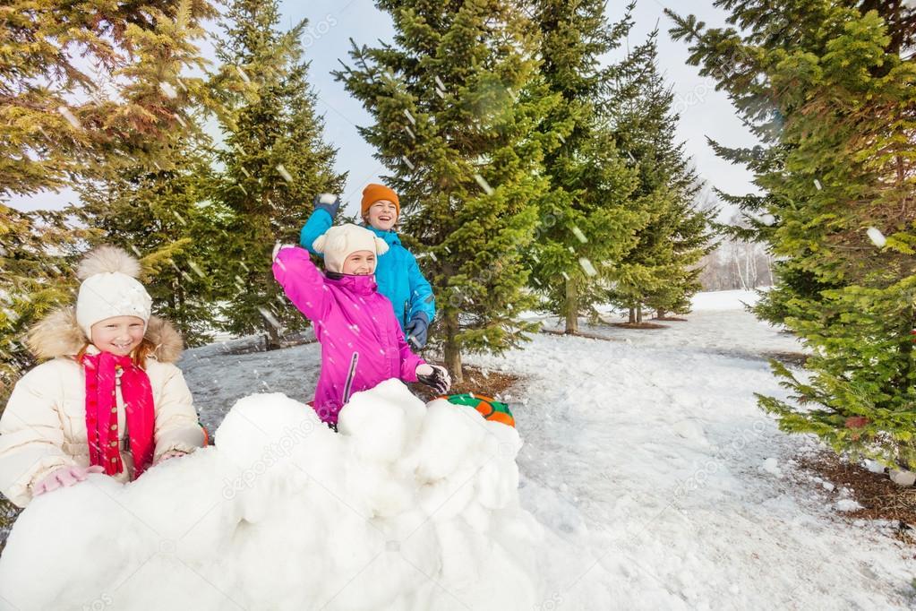 Girls and boy playing snowballs game
