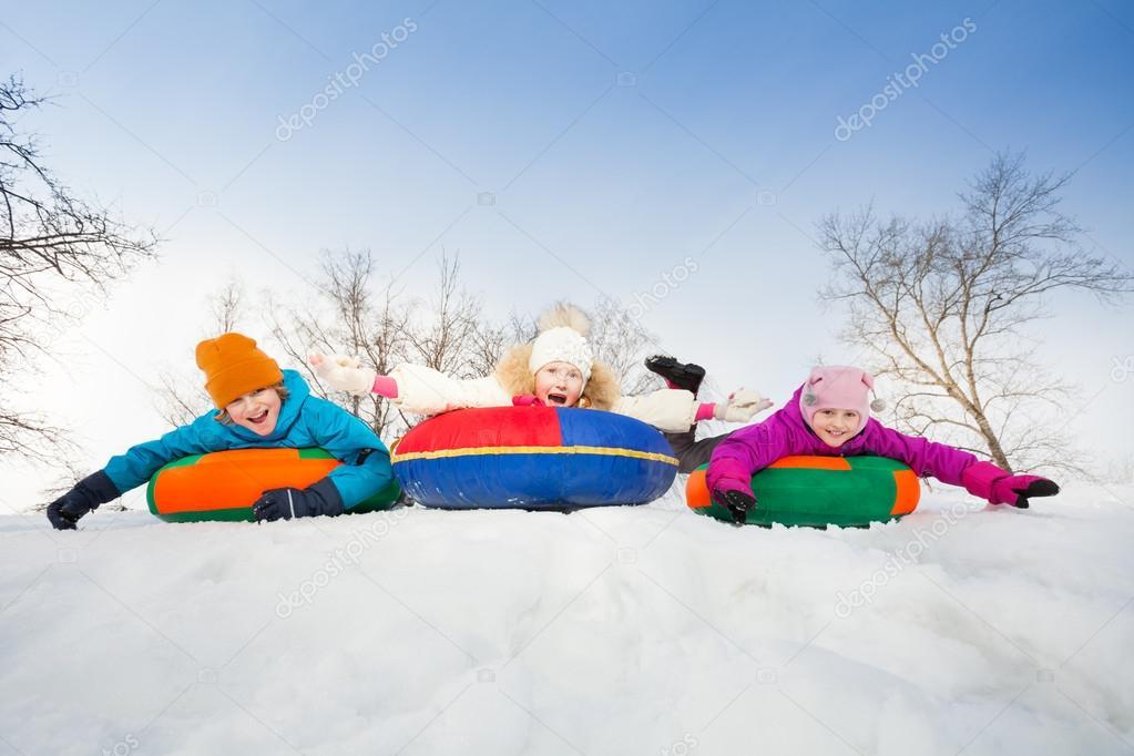 Happy group of children slide on tubes