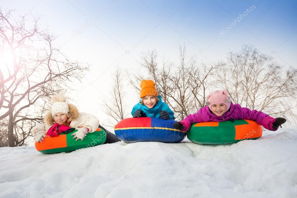 Row of children sliding down on tubes