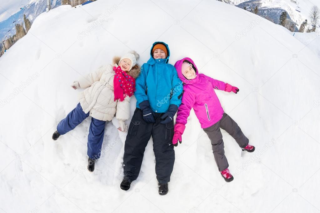 Three kids lay on snow