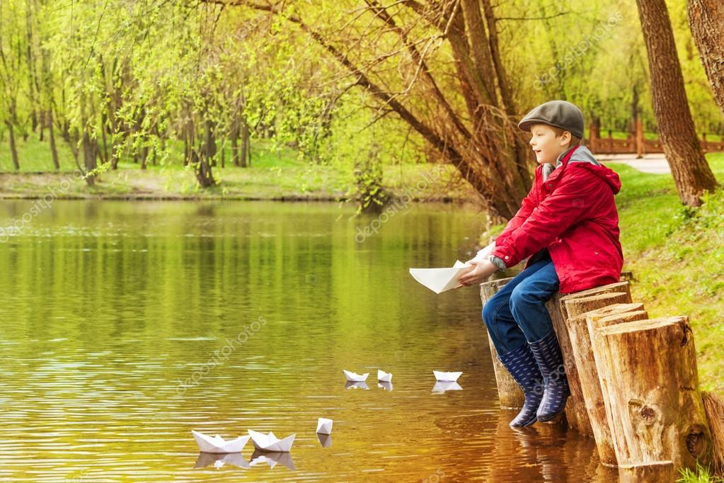 Boy playing with  paper boats