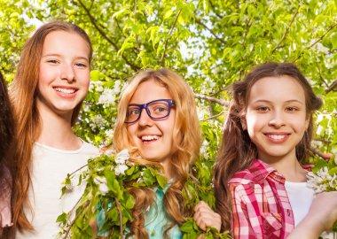 Three teenage girls holding branches