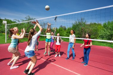 Teenage girls and boy play volleyball
