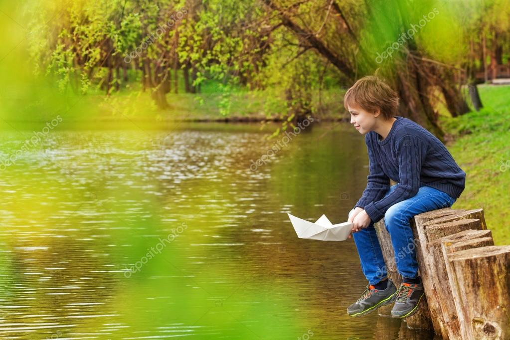 Cute boy holding paper boat