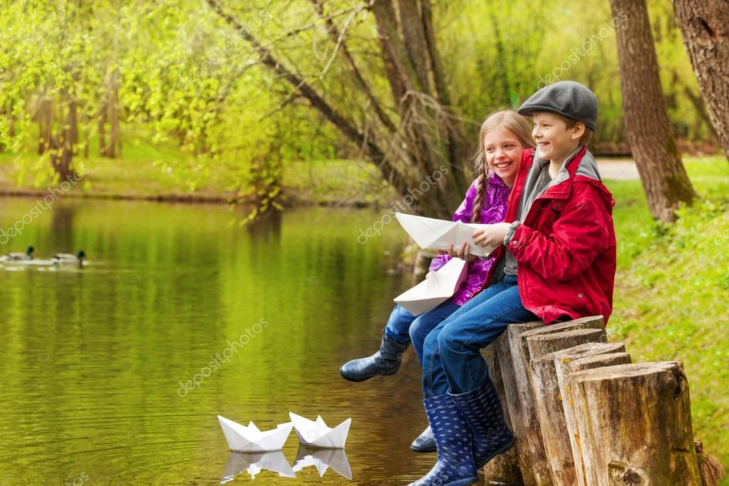 Laughing girl and boy with paper boats