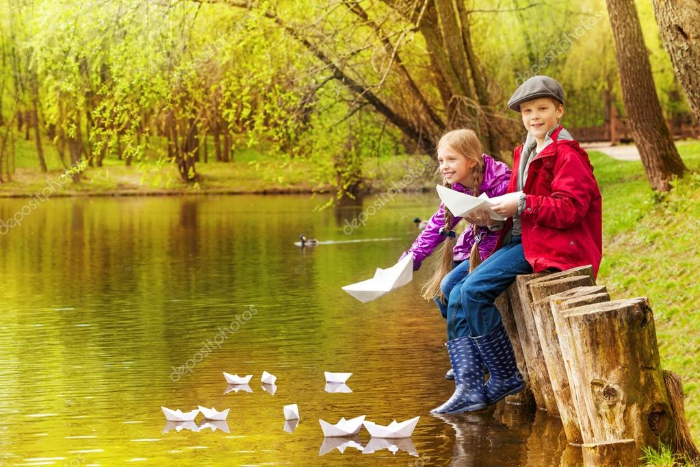 girl and boy play with paper boats