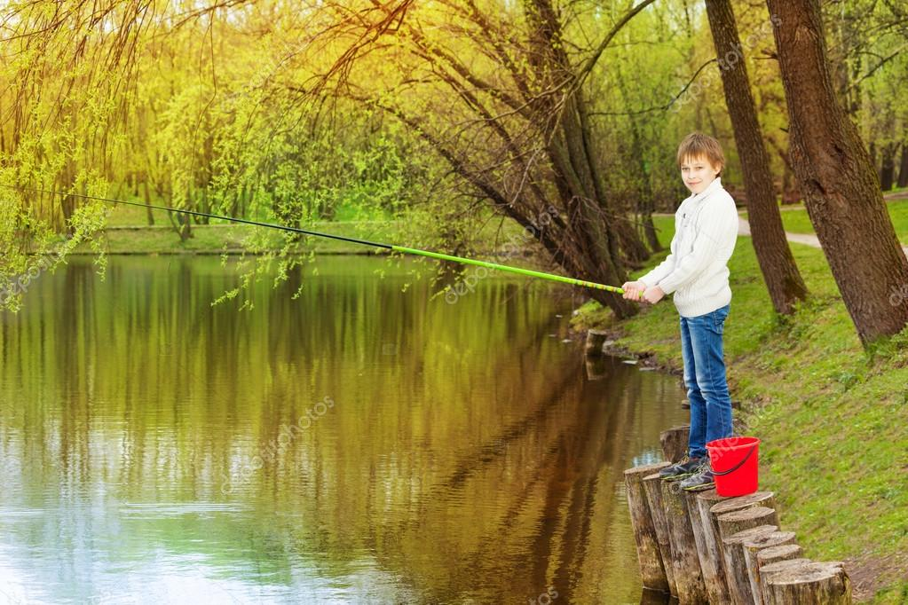 Boy standing and fishing near pond