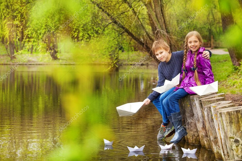 Boy and girl putting paper boats