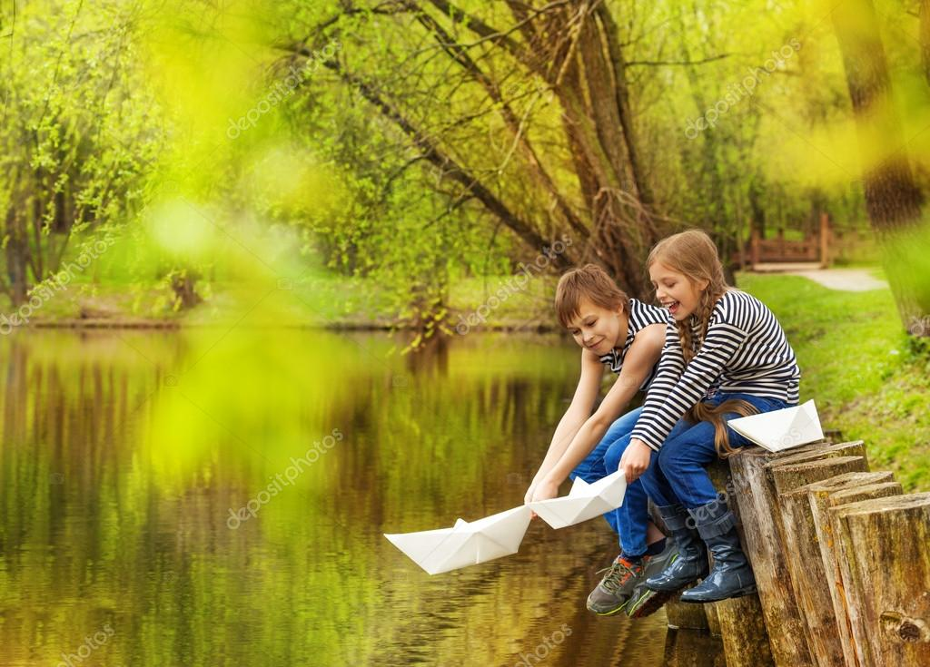 Boy and girl play with paper boats