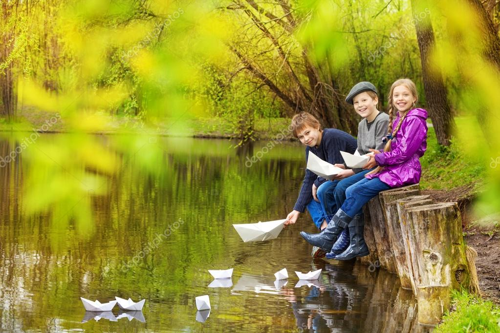 friends putting paper boats on pond