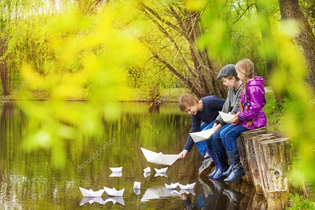 Three kids putting paper boats