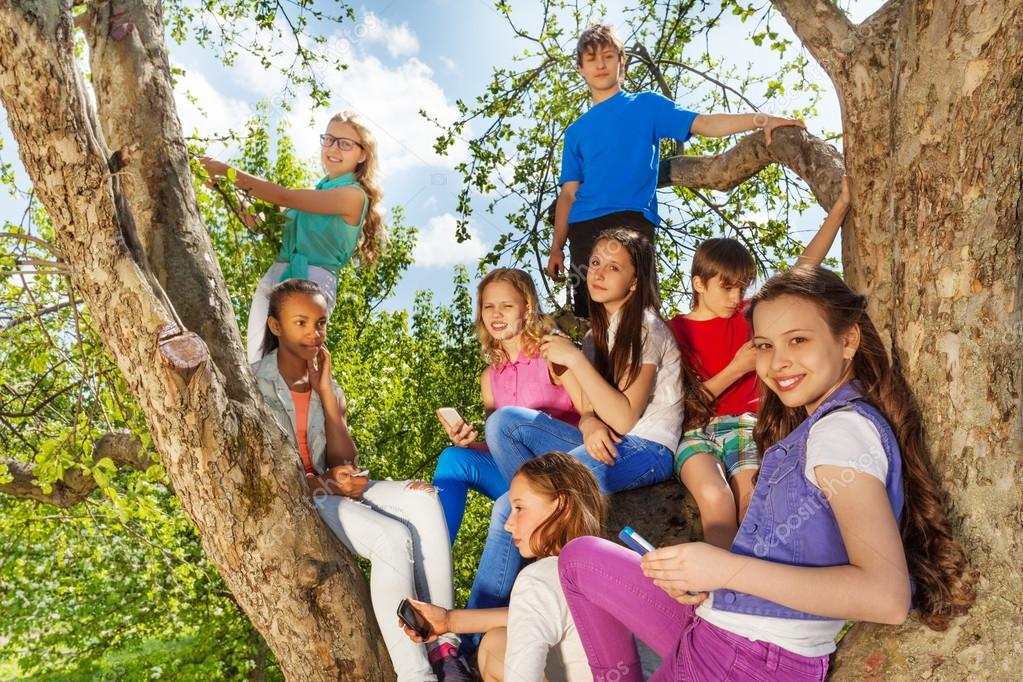 teens on tree with mobiles