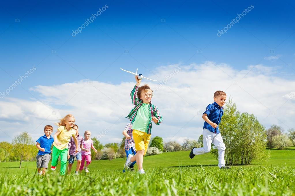 Running boy with airplane toy and children