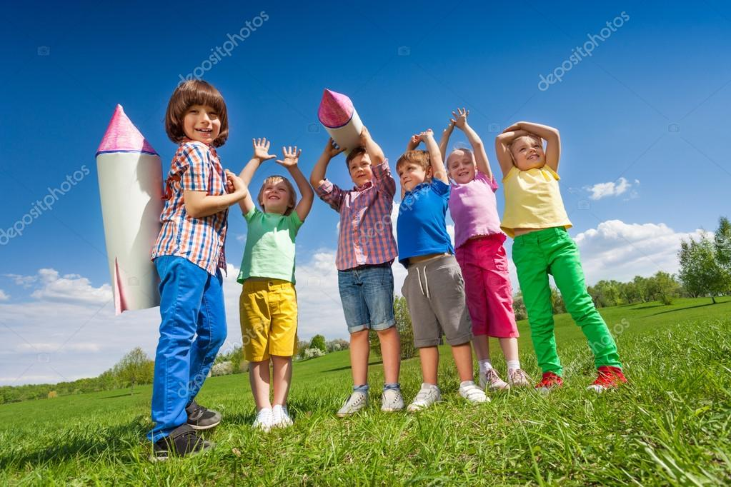 children stand with paper rocket toy